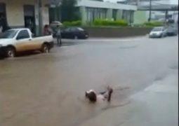 Homem é flagrado nadando na enxurrada no centro de Carmo do Paranaíba