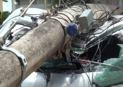 Carro fica danificado ao ser atingido por poste derrubado por caminhão na cidade de Patos de Minas